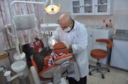 Dentist Antone  is examining one of the beneficiaries in Shija'ia Dental Clinic
