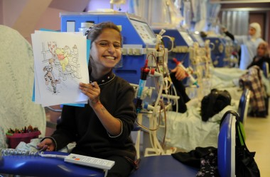 A pediatric dialysis patient at the Lutheran World Federation's Augusta Victoria Hospital proudly displays the coloring she has done as part of the psycho-social care facilitated for children in the hospital's Specialized Child Care Center. Photo by K.Brown