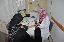 Midwife Wisal   is examining a pregnant woman during antenatal care in Darraj clinic